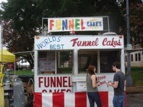 Festival goers wait on an order of funnel cakes at the Athens Grease Festival in Athens, Alabama.
