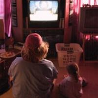 picture of kids sitting in floor watching a television