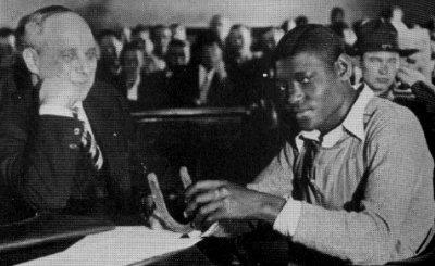 Attorney Samuel Leibowitz sitting with Haywood Patterson with his good luck horseshoe. Patterson was one of the nine young black men convicted of raping two white women.