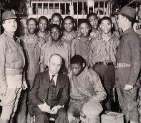The Scottsboro Boys, with their attorney, under guard by the state militia.