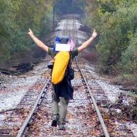 Hiker walking down train tracks