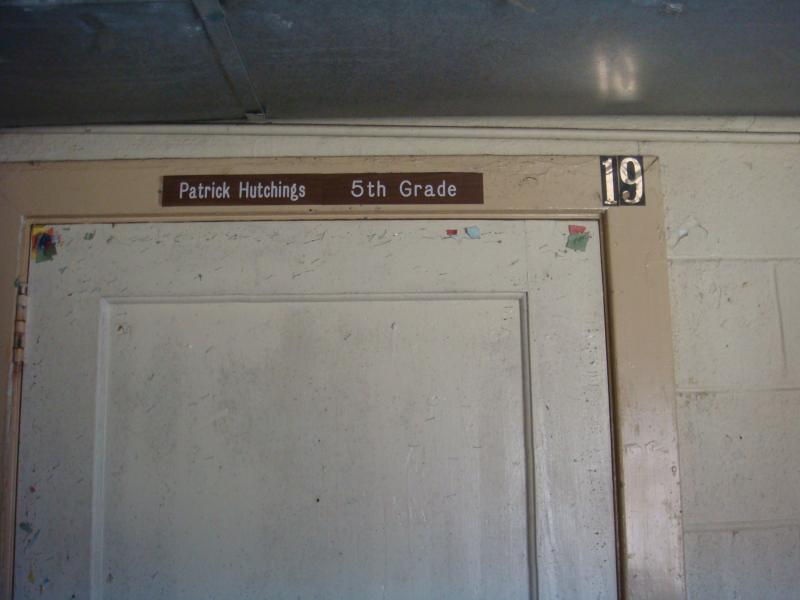City Hall was once the local school. Much of the building is in disrepair with leaky ceilings and peeling paint. Here, a teacher's nameplate remains over an old classroom.