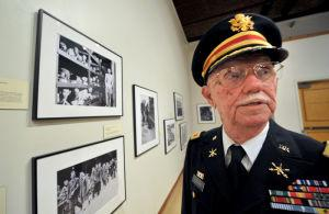 Major (Retired) Edward B. Ledford looks over photographs during the opening of an exhibition of WWII photos from Associated Press photographers at the Wiregrass Museum of Art.