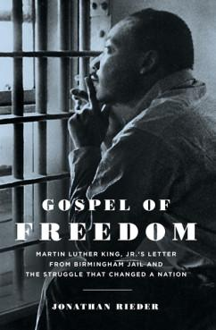 Black and white photo of Dr. King looking sitting and looking out through prison bars