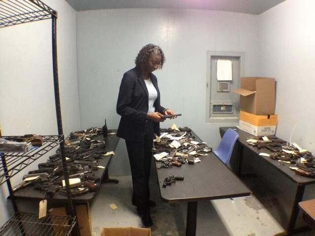 Prattville Police Capt. Diane Hamm looks over guns to be sold. The money raised will help the department buy uniforms and equipment.