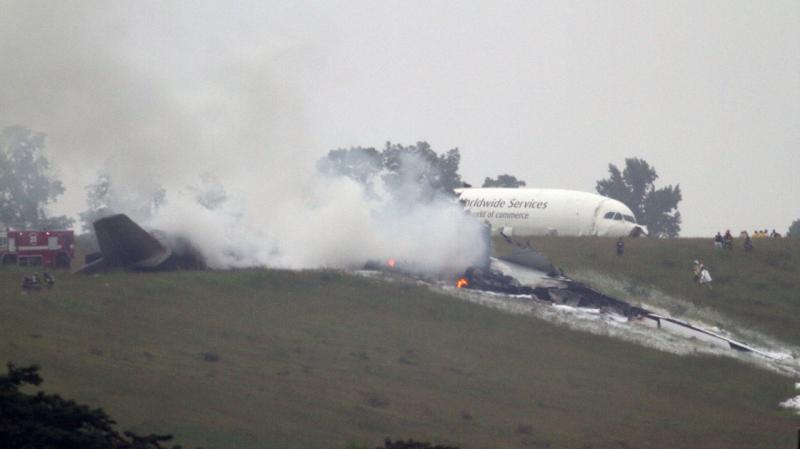 Debris burns as a UPS cargo plane lies on a hill near Birmingham-Shuttlesworth International Airport after crashing August 14, 2013.
