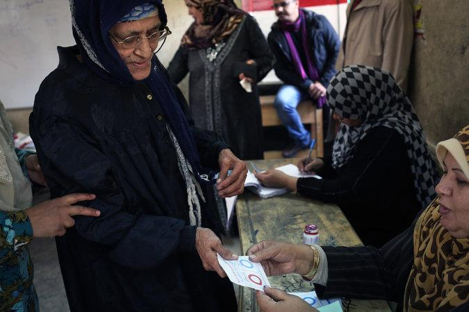 An Egyptian woman a ballot for the constitutional referendum at a polling station in Cairo.