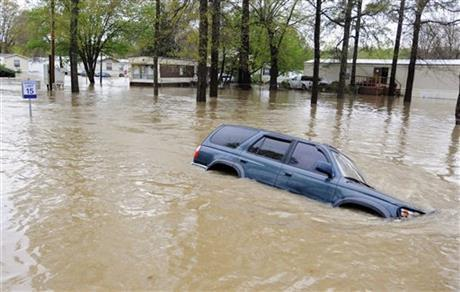 An abandoned vehicle sits submerged by floodwaters on a road in a mobile home park in Pelham, Ala., on Monday, April 7, 2014. Storms dumped torrential rains in central Alabama overnight, causing flooding across the region. (AP Photo/Jay Reeves)