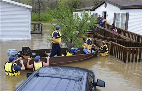 Firefighters rescue a family from their home, surrounded by floodwaters, in a mobile home park in Pelham, Ala., on Monday, April 7, 2014. Overnight storms dumped torrential rains in central Alabama, causing flooding across a wide area. (AP/Jay Reeves)