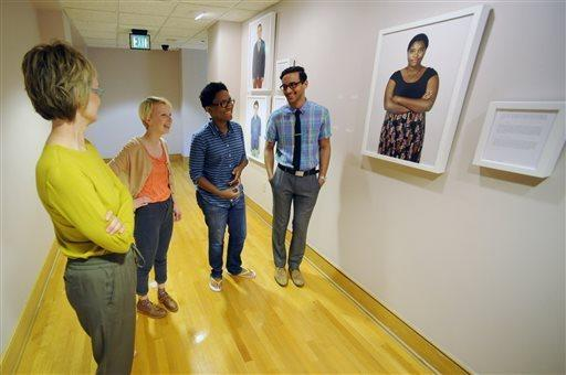 In this photo taken on Monday, April 21, 2014, photographer Carolyn Sherer, left, looks at her new exhibit featuring images of young people with varied sexual identities and preferences during the installation work in Birmingham