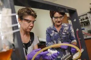 Drs. Gabriela Gurau, left, and Julia Shamshina work in a UA lab with an electrospinning apparatus (Jeff Hanson).