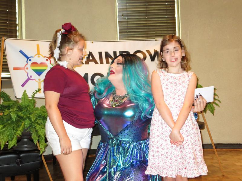 "Wade Brasfield, AKA Khloe Kash, with two you audience members during ""Drag Queen Stiry Hour."""