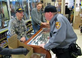 Frank Whitmore (right) speaks with Ron Darnall (left) at his gun shop west of Bloomington, Ill.