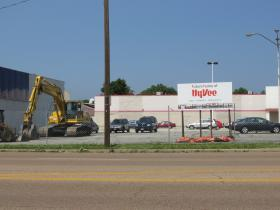 an excavator sits in front of 2115 S. MacArthur Boulevard as demolition begins to prepare for future home of Hy-Vee