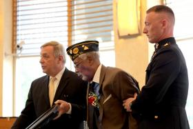 Sen. Dick Durbin, left, presents the Congressional Gold Medal to World War II Marine DeLoyce McMurray at the Abraham Lincoln Presidential Library in Springfield. Marine Maj. Greg Gordon, right, helped the 87-year-old McMurray stand during the ceremony.