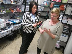 Regional superintendent Keri Garrett (left) and Kathy Donnelly go through the list of donated items for children in Donnelly's office storeroom.