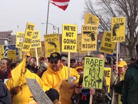 Pro-gun ralliers march toward the Statehouse on Wednesday. Signs like the one in the foreground express the rationale that women are better protected from would-be attackers with the right to carry.