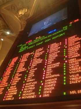 An Illinois House voting board in December shows the results for what would become a pension overhaul law.