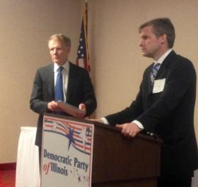 Attorney Mike Kasper stands at the podium, as House Speaker and Democratic Party of Illinois Chairman Michael Madigan looks on, at a recent Party meeting in Springfield.  Kasper, a Madigan ally, has been hired by a group of taxpayers seeking to dismiss two citizen's initiatives.
