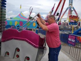 An inspector from the Illinois Department of Labor checks a carnival ride on the Illinois State Fairgrounds Wednesday.