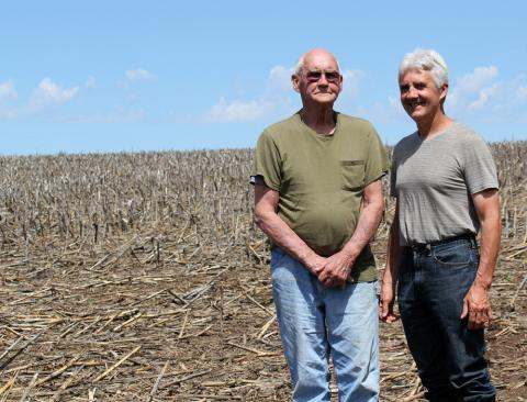 Father and son Jim and Tom Arganbright stand in a field that Tom planted with soybeans this spring. The older generation still owns the land, but Tom now rents it as part of his own farming operation.