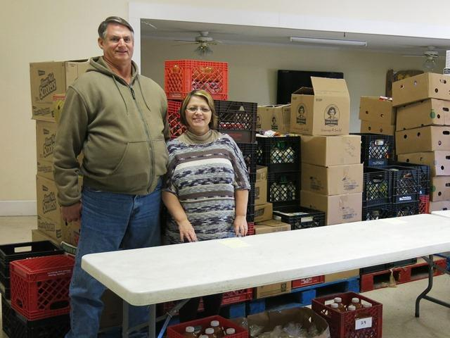 Pastors Curt and Kim Matthews stand in the food pantry behind their church in Odin, Illinois.  The number of hungry families and seniors they serve has increased nine fold in the past 16 years.