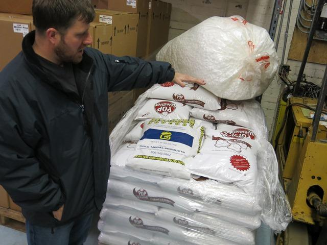 Wilcutt indicates how high his stack of popcorn seed bags would be if 2013 prices were lower.