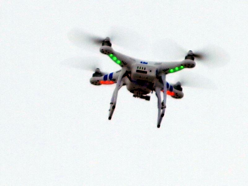 A remote-controlled quadcopter hovers over a Bloomington, Illinois, parking lot, where Chad Colby of AgTechTalk.com offered test flights of new unmanned vehicle models.