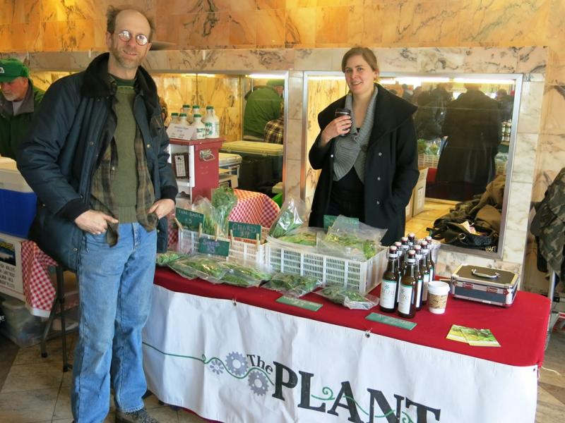 John Edel (left), founder of the social enterprise vertical farm, raises money for research and education by selling at neighborhood farmers markets.