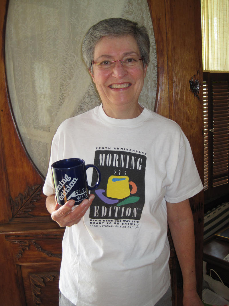 "Attached is my ""mug shot"" holding my WSSR mug and wearing my Morning Edition 10th Anniversary T shirt!  I'm glad your recent fund drive was successful.  I'm looking forward to receiving this year's mug."