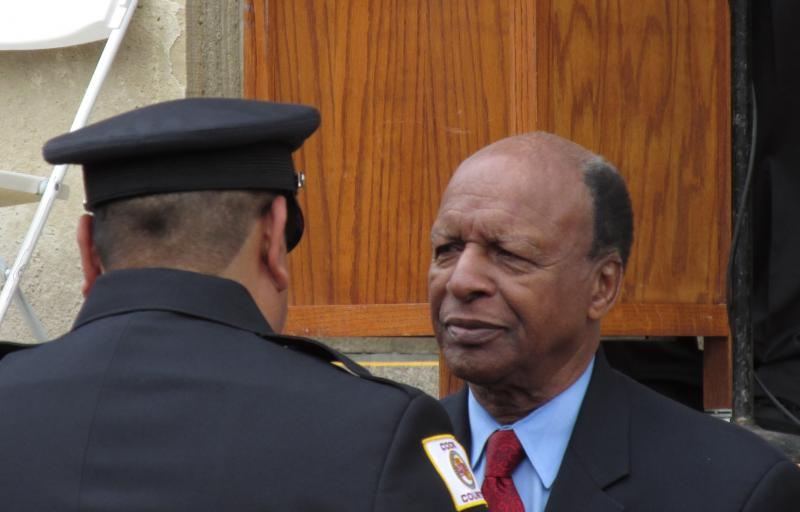 Secretary of State Jesse White (D) shakes hands with a police officer at Thursday's Police Memorial outside the Capitol in Springfield.