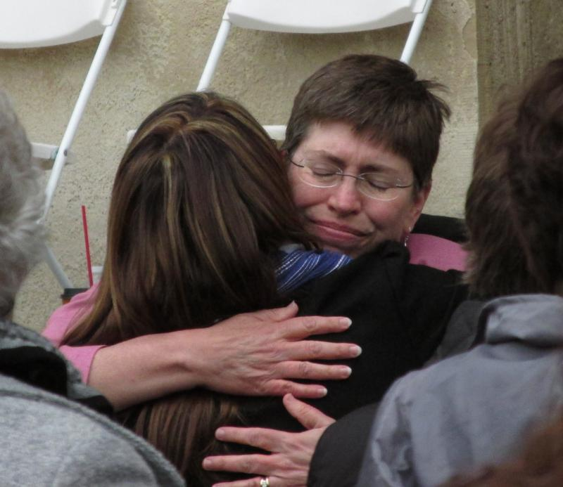 Lt. Gov. Sheila Simon (D) hugs a family member of a fallen police officer.
