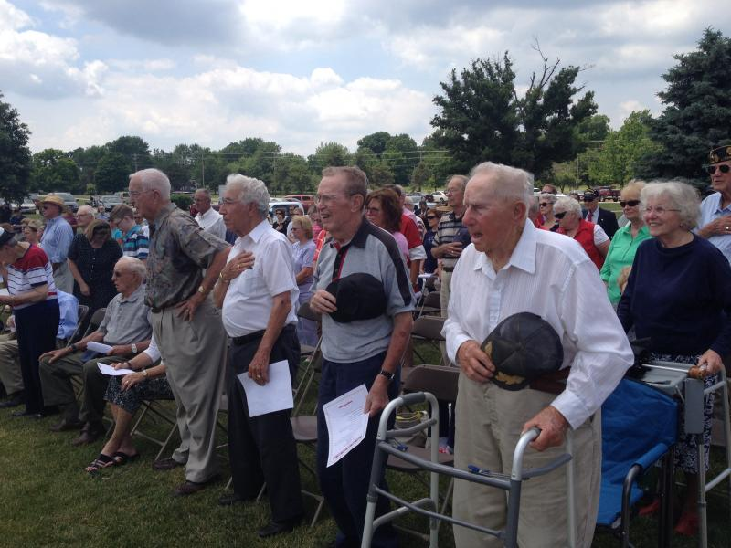 WWII veterans observe the flag during the National Anthem at a D-Day memorial on Friday.