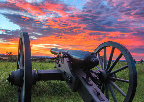 July skies are fiery over a Union artillery position on the northern end of  Cemetery Ridge, the center of the Union line, where it joins Cemetery Hill north of the copse of trees. This position is overlooking the broad valley down to Seminary Ridge.