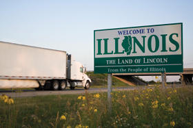 """Semi-trailer truck passing a """"Welcome to Illinois"""" sign"""