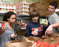 Rosa Pergams, Griffin Berg, and Riley Newman fills bags with basic food items that will be distributed to waiting families at the Oak Park River Forest Food Pantry in Oak Park, IL.