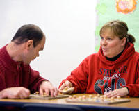 Streator Unlimited staff member Sue Donnell helps client Jim Young complete wooden puzzles during classroom activities. Roughly 80 percent of the organization's budget comes from the state, which was six months behind on payments to Streator Unlimited