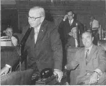 Southern Illinois powerhouse Paul Powell is speaking from the floor of the Illinois House of Representatives. Fellow southern Illinoisan Clyde Choate is seated beside him. In the background between them is John P.