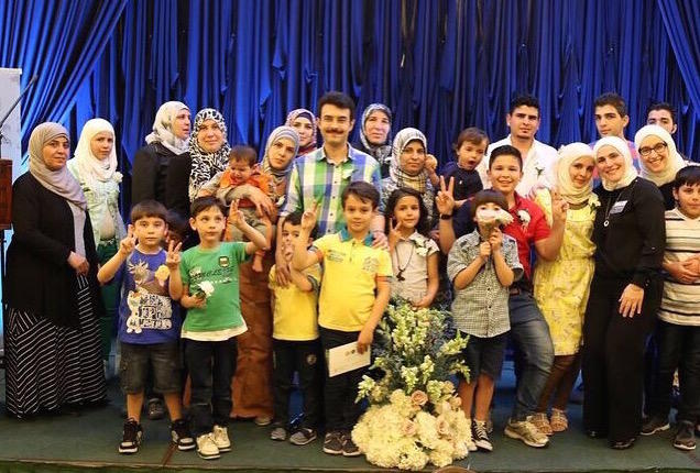 Chicago area Syrian refugees gather for a group picture at a Syrian Community Network event honoring World Refugee Day in June.