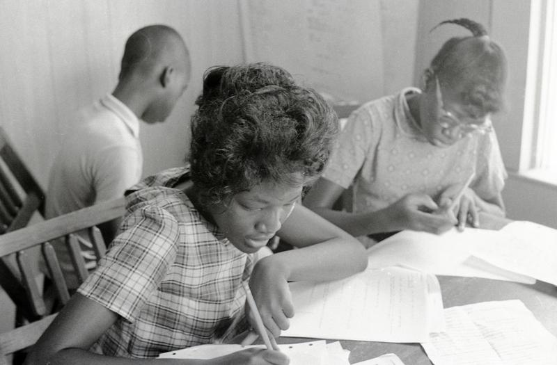 """'Students Margaret Dwight (left) and Alice Dwight (right) write at their desks in the Freedom School at Mt. Zion Baptist Church in Hattiesburg, Mississippi."""""""