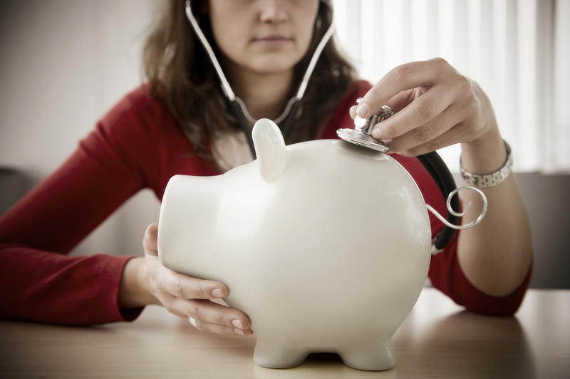 Examining Financial Health (stethescope on piggy bank)