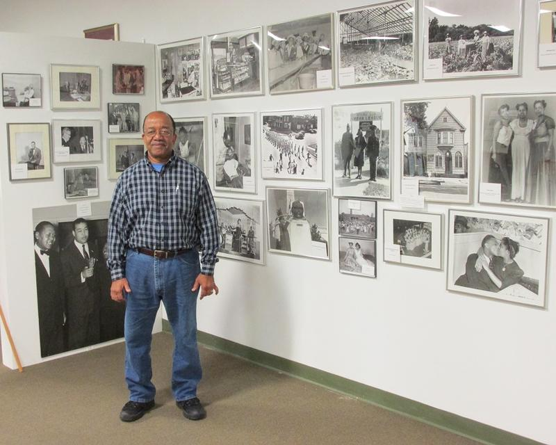 "board president and acting director, Doug King, standing in front of photographs by Eddie Winfred Helm, aka ""Doc"""