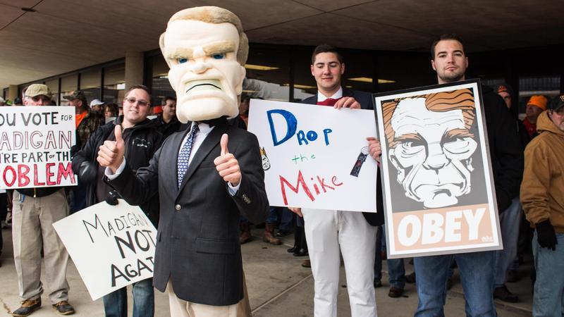 Protester wearing oversize Madigan mascot head.