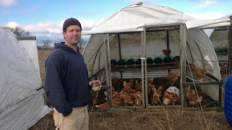 Man standing in front of a tent full of chickens.