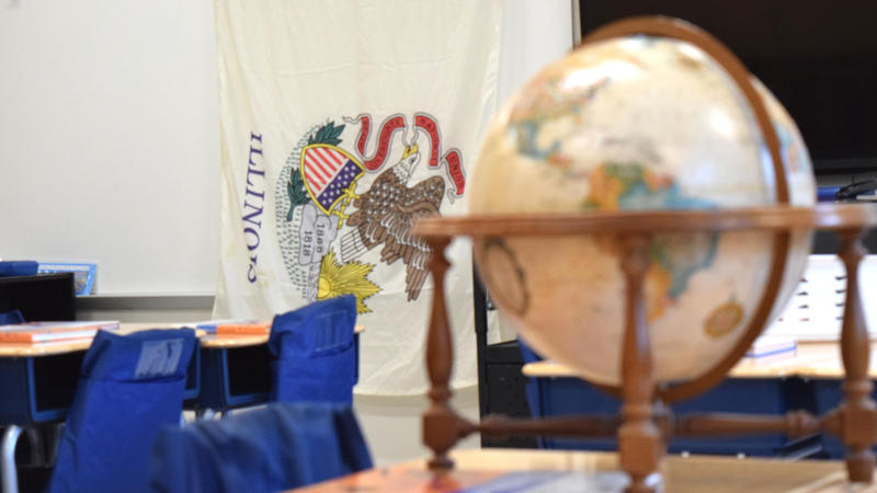 A globe in a classroom with the Illinois flag in the background.