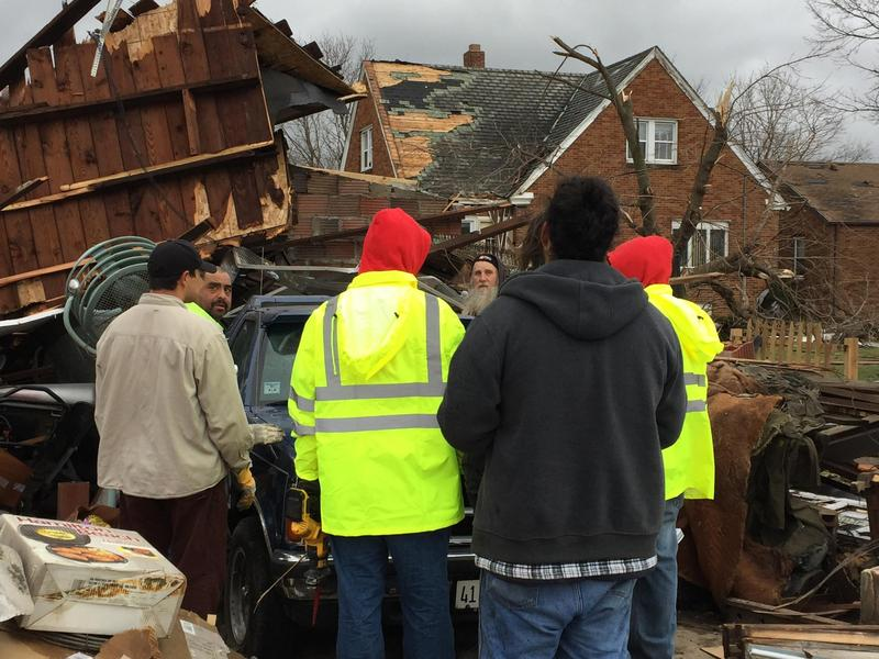 Workers in Naplate surrounded by debris