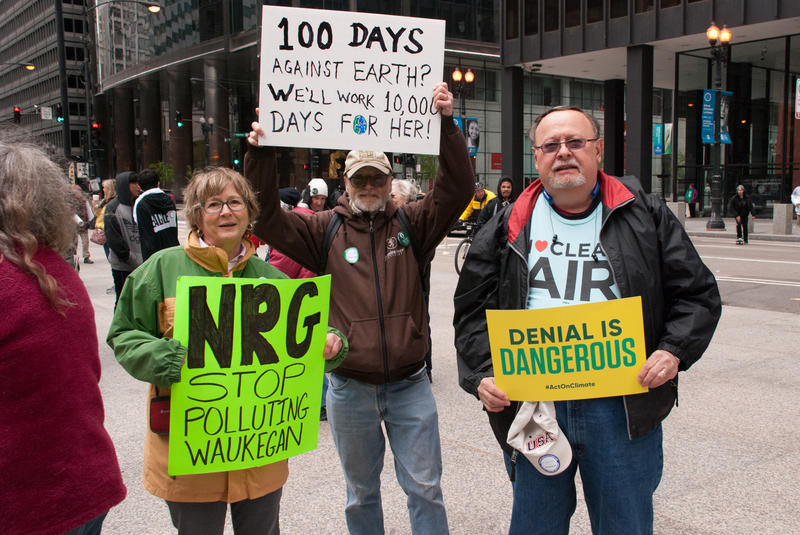 Protesters display signs at an April climate rally.