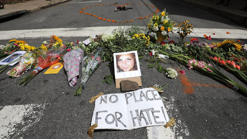 Flowers surround a photo of 32-year-old Heather Heyer, who was killed when a car plowed into a crowd of people protesting against the white supremacist Unite the Right rally in Charlottesville, Va.