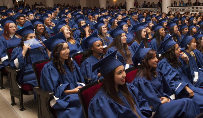 seated students in graduation gowns and caps