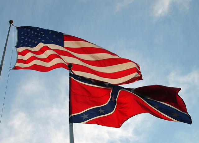 A confederate flag flies under a U.S.A. flag